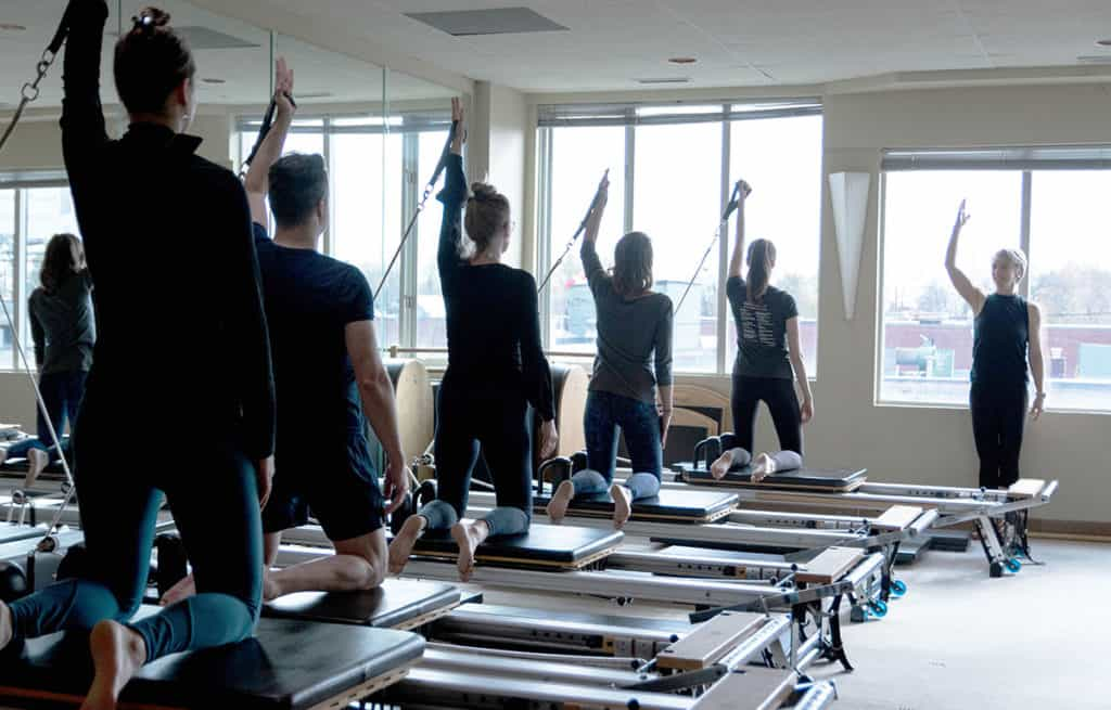 Instructor and student group on pilates reformers captioned 'Pilates Reformer Classes'